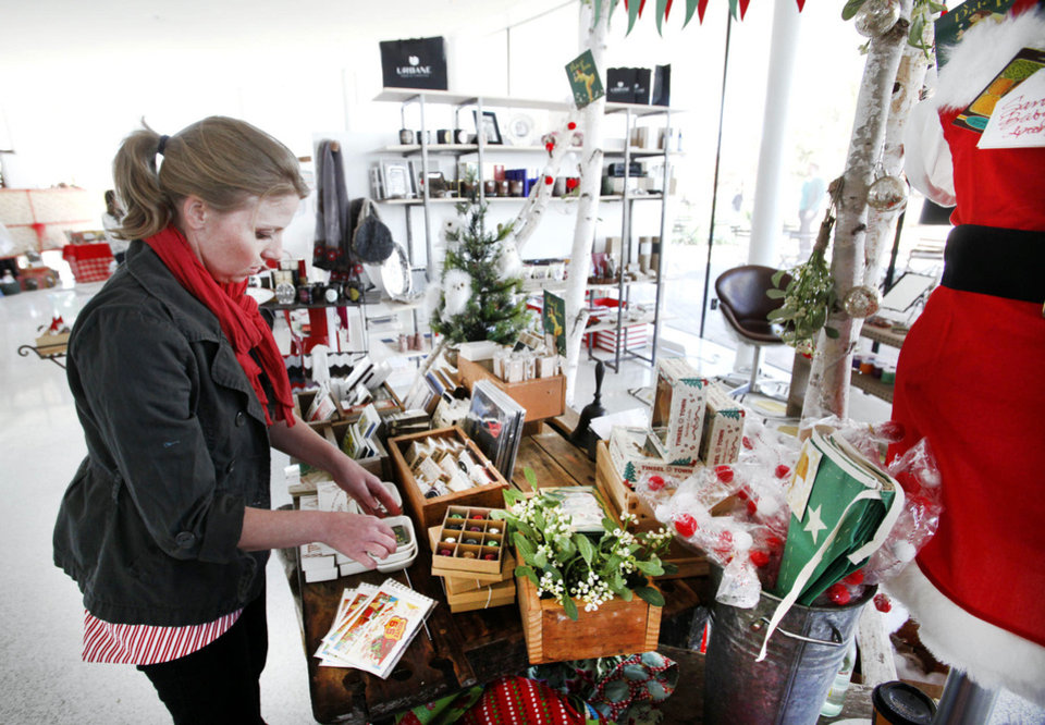 Stephanie Humes straightens up merchandise Friday at A Date With Iris, a pop-up shop in the Myriad Gardens in Oklahoma City. Photo By Steve Gooch, The Oklahoman