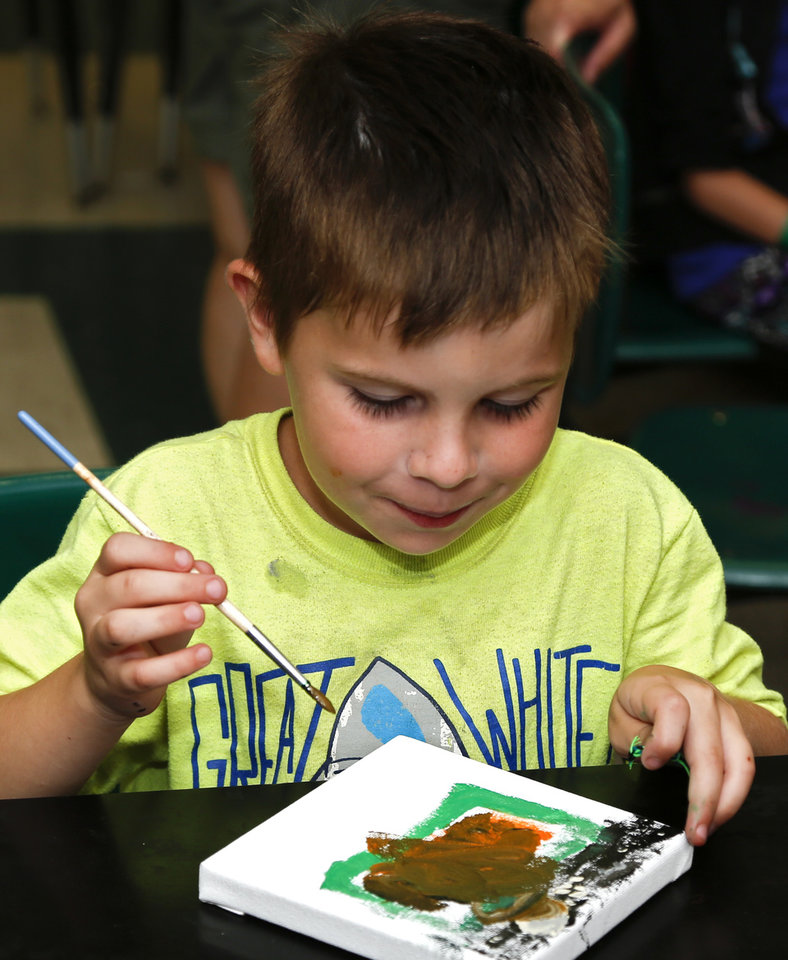 Photo -  Bryden, 7, paints during an arts and crafts time in which campers were asked to paint what hope meant to them. [Photo by Kurt Steiss, The Oklahoman]