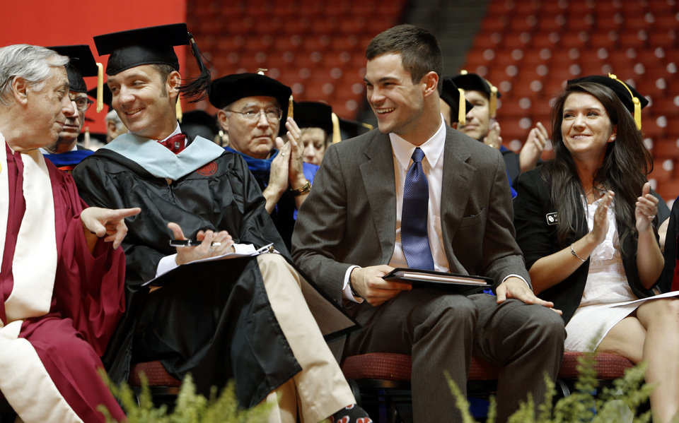 Photo - Max Weitzenhoffer, left, and Clark Stroud speak as Joe Sangirardi, president of the OU Student Association, is called to the podium while Kayley Williamson, vocalist who sang the national anthem, watches during the 2012 Convocation Ceremony at the Lloyd Noble Center on Thursday in Norman.     Photo by Steve Sisney, The Oklahoman  STEVE SISNEY - THE OKLAHOMAN