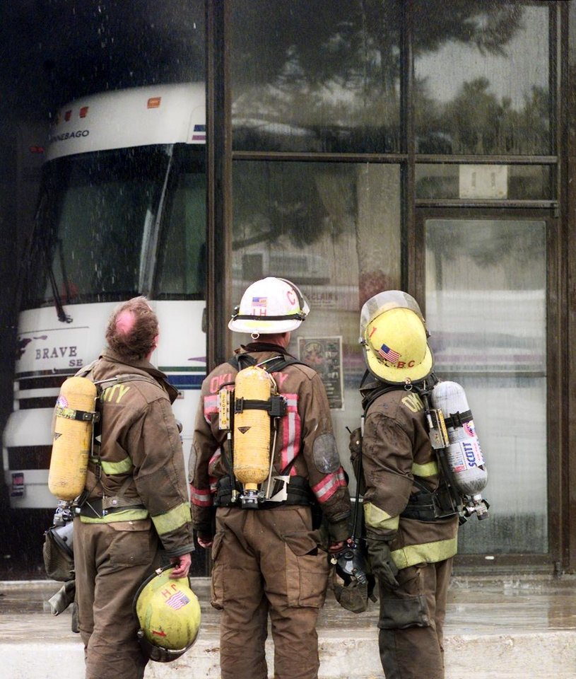 Photo - OKC assistant chief Jon Hansen, center, and two other firefighters look at damage to showroom caused by a 4- alarm fire around noon Monday at Reno and Rockwell.