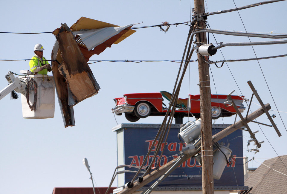 A utility worker tries to free storm debris suspended in a power line in Branson, Mo., Wednesday, Feb. 29, 2012. An apparent tornado hopscotched through the city's main tourist district overnight, causing damage for miles. (AP Photo/Mark Schiefelbein)  ORG XMIT: MOMS121