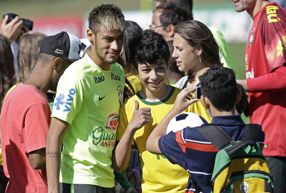 Photo - Brazil's Neymar poses for pictures with fans prior to a training session in Teresopolis, Brazil, Wednesday, June 25, 2014. About fifty children that were victims of floods and landslides in Rio de Janeiro state in 2011 watched the training. Brazil will face Chile on June 28 in the round of 16 of the 2014 soccer World Cup. (AP Photo/Andre Penner)