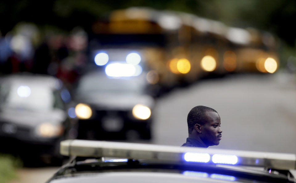 Photo - A Dekalb County Police officer stands guard as students from Ronald E. McNair Discovery Learning Academy board school buses to take them to reunite with their parents after they were evacuated after reports of a gunman entered the school, Tuesday, Aug. 20, 2013, in Decatur, Ga. All students and teachers are safe and a suspect is in custody after gunfire was heard at the Atlanta-area elementary school today. (AP Photo/David Goldman)