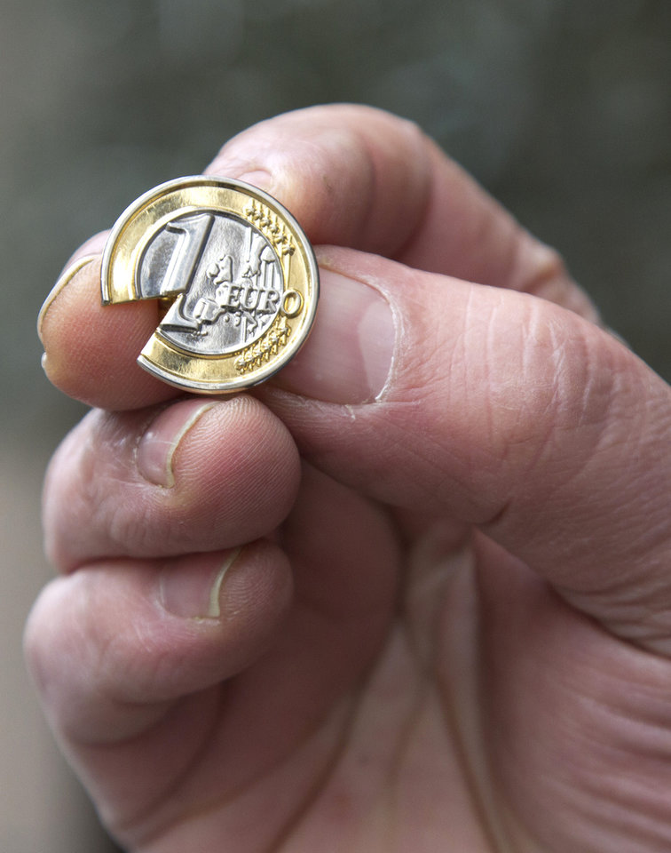 Photo - A Cypriot man, who did not wish to be identified, holds up a souvenir Cypriot euro coin lapel pin with a piece taken out near the Cypriot delegation building in Brussels on Sunday, March 24, 2013. The EU says a top official will chair a high-level meeting on Cyprus in a last-ditch effort to seal a deal before finance ministers decide whether the island nation gets a 10 billion euro bailout loan to save it from bankruptcy. (AP Photo/Virginia Mayo)