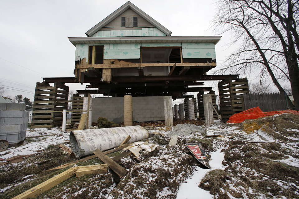Photo - A small home damaged by Superstorm Sandy is braced in the air Tuesday, Feb. 5, 2013,  in Union Beach, N.J., as workers raise it to prevent future flooding.  New Jersey Gov. Christie told a gathering in Union Beach Tuesday that the National Flood Insurance Program's handling of claims in New Jersey