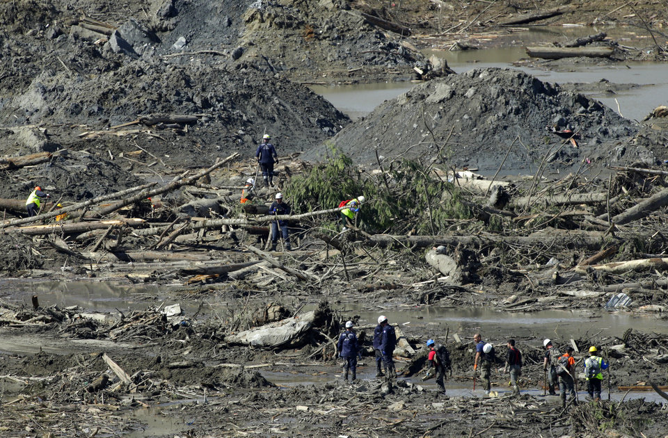 Photo - Workers search for victims and clear debris, Tuesday, April 1, 2014, near Darrington, Wash., at the site of the deadly mudslide that hit the community of Oso,Wash. on March 22, 2014. (AP Photo/Ted S. Warren)