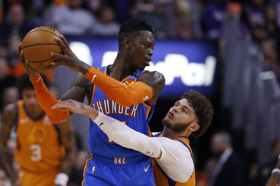 Photo - Phoenix Suns guard Tyler Johnson, right, defends against Oklahoma City Thunder guard Dennis Schroder, left, during the second half of an NBA basketball game Friday, Jan. 31, 2020, in Phoenix. The Thunder defeated the Suns 111-107. (AP Photo/Ross D. Franklin)
