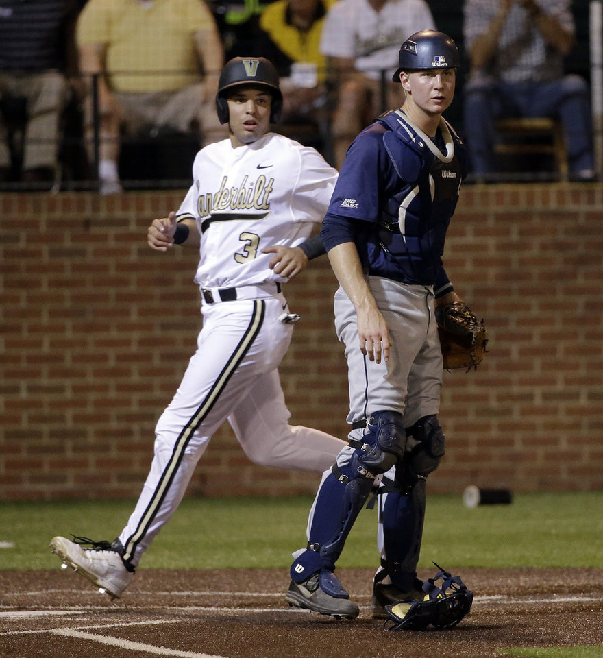 Photo - Vanderbilt's Vince Conde (3) scores on a double by Xavier Turner as Xavier catcher Daniel Rizzie, right, watches for a throw during the fourth inning of an NCAA college baseball tournament regional game Friday, May 30, 2014, in Nashville, Tenn. (AP Photo/Mark Humphrey)