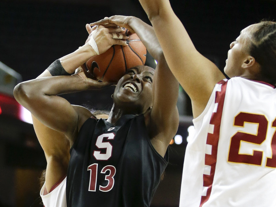 Photo - Stanford forward Chiney Ogwumike, middle, pulls in a rebound between Southern California forward Alexyz Vaioletama, right, and guard Kiki Alofaituli during the first half of an NCAA women's basketball game in Los Angeles, Friday, Feb. 15, 2013. (AP Photo/Chris Carlson)