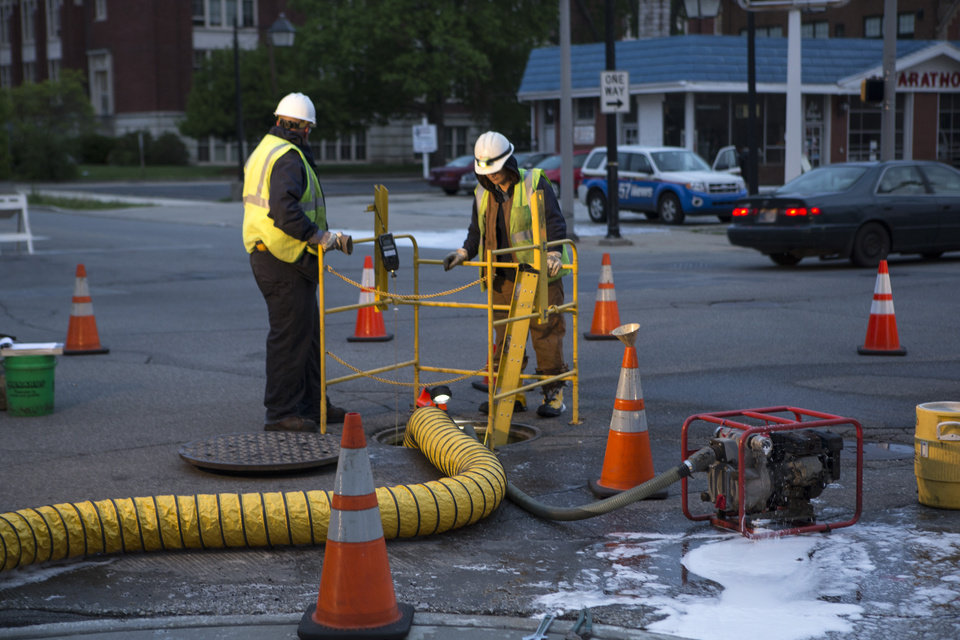 Photo - AEP employees work assesing the damage caused by a fire in underground vault near the intersection of Washington and Lafayette Street in South Bend on Friday May 16, 2014.  An underground electrical fire left hundreds of homes and businesses in downtown South Bend without power Friday as thousands of people are in town for the University of Notre Dame's weekend commencement ceremonies. (AP Photo/South Bend Tribune, Santiago Flores)