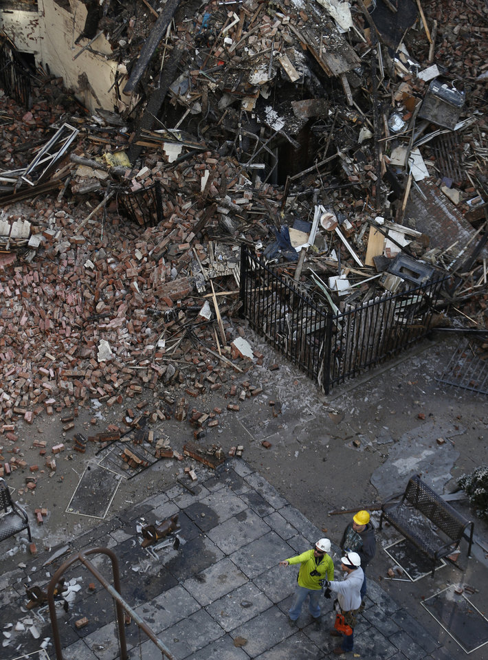 Photo - Workers survey an area covered in rubble Friday, March 14, 2014, two days after a natural gas explosion leveled two apartment buildings in New York. Using sound devices to probe for voices and telescopic cameras to peer into small spaces, workers searching a pile of rubble from a gas explosion in the East Harlem section of Manhattan, continued to treat it as a rescue operation, holding onto the possibility of finding survivors from a blast that brought down two apartment buildings and killed at least eight people. (AP Photo/Julio Cortez)