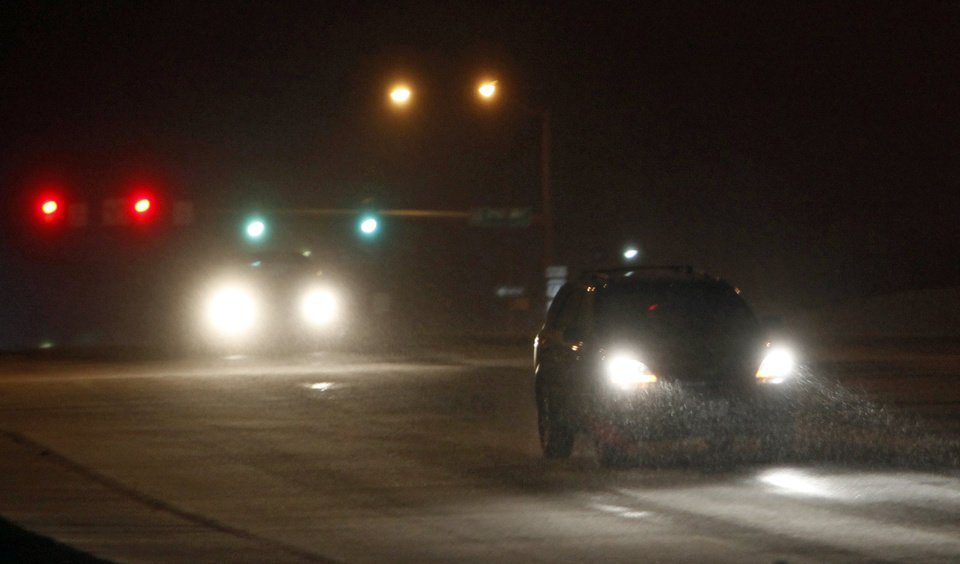 Photo - Sleet is shown in the headlights of a vehicle on Britton Rd. near Broadway in Oklahoma City, late Monday, January 31, 2011. Photo by Nate Billings, The Oklahoman