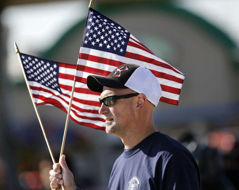 Photo - A man carries two American flags while marching with people representing AFSA at Tinker Air Force Base in the Midwest City Veteran's Day Parade on Friday, Nov. 10, 2017. The Air Force Sergeants Association (AFSA) is a non-profit organization representing the professional and personal interests of nearly 111,000 active, retired and veteran total enlisted members of the United States Air Force and their families.  Photo by Jim Beckel, The Oklahoman