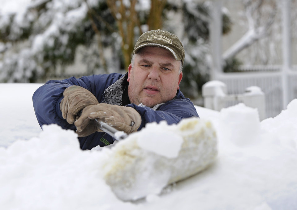 Photo - Hank Luth brushes snow piled high on his car parked in his driveway on Terry Ct. after a snow storm on Saturday, Feb. 9, 2013 in Glen Head, N.Y. (AP Photo/Kathy Kmonicek)