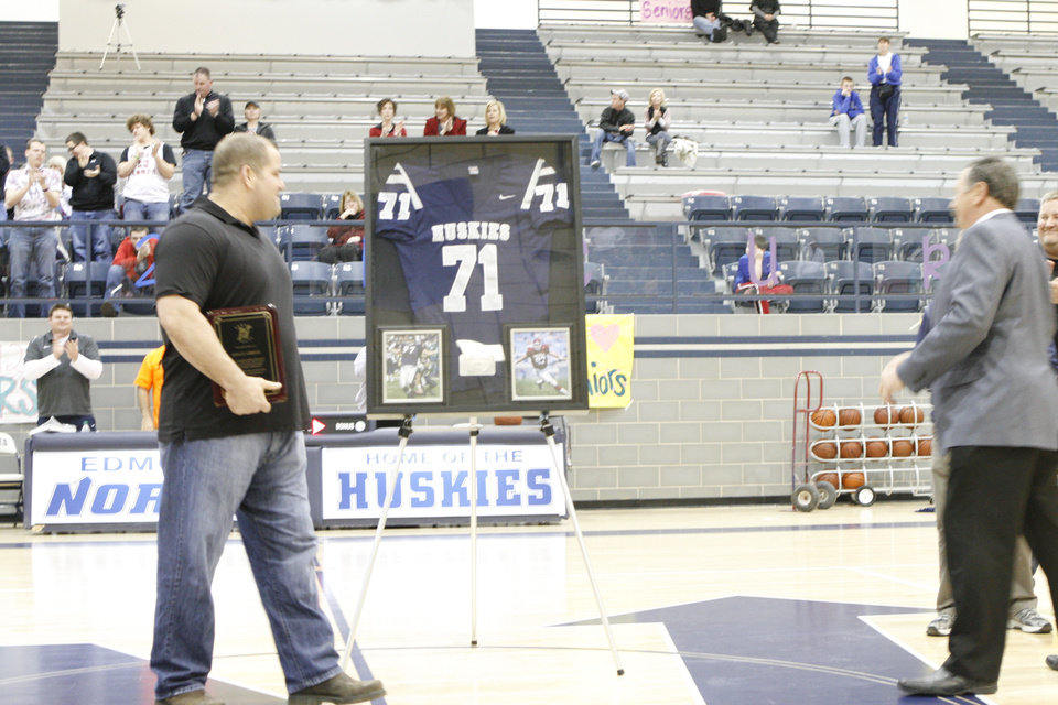 Former NFL player Kelly Gregg, left, looks at his retired Edmond North High School football jersey during a halftime ceremony during Tuesday's boys basketball game. Gregg graduated from Edmond North in 1995. PHOTO BY JASON KERSEY, THE OKLAHOMAN