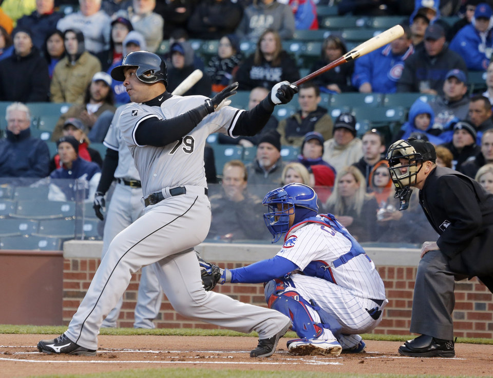 Photo - Chicago White Sox's Jose Abreu hits a sacrifice fly off Chicago Cubs starting pitcher Jeff Samardzija, scoring Alejandro De Aza, during the first inning of an interleague baseball game Monday, May 5, 2014, in Chicago. (AP Photo/Charles Rex Arbogast)