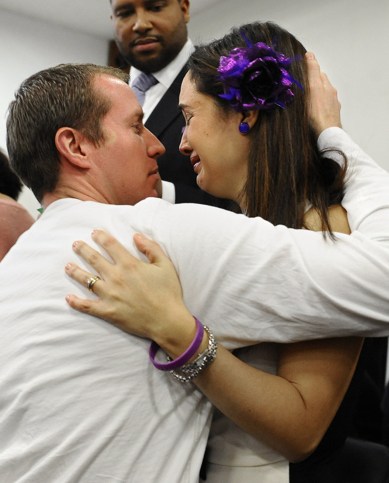Photo - Robbie Parker, father of Sandy Hook School shooting victim Emilie Parker, embraces Nelba Marquez-Greene, mother of victim Ana Marquez-Greene at the end of a news conference at Edmond Town Hall in Newtown, Conn., Monday, Jan. 14, 2013. One month after the mass school shooting at Sandy Hook Elementary School, the parents joined a grassroots initiative called Sandy Hook Promise to support solutions for a safer community. (AP Photo/Jessica Hill)