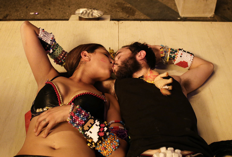 Photo - Maggie Sanchez, left, and Chad Wry, both of Riverside, Calif., kiss beneath an art installation at the Electric Daisy Carnival Friday, June 20, 2014, in Las Vegas. (AP Photo/John Locher)