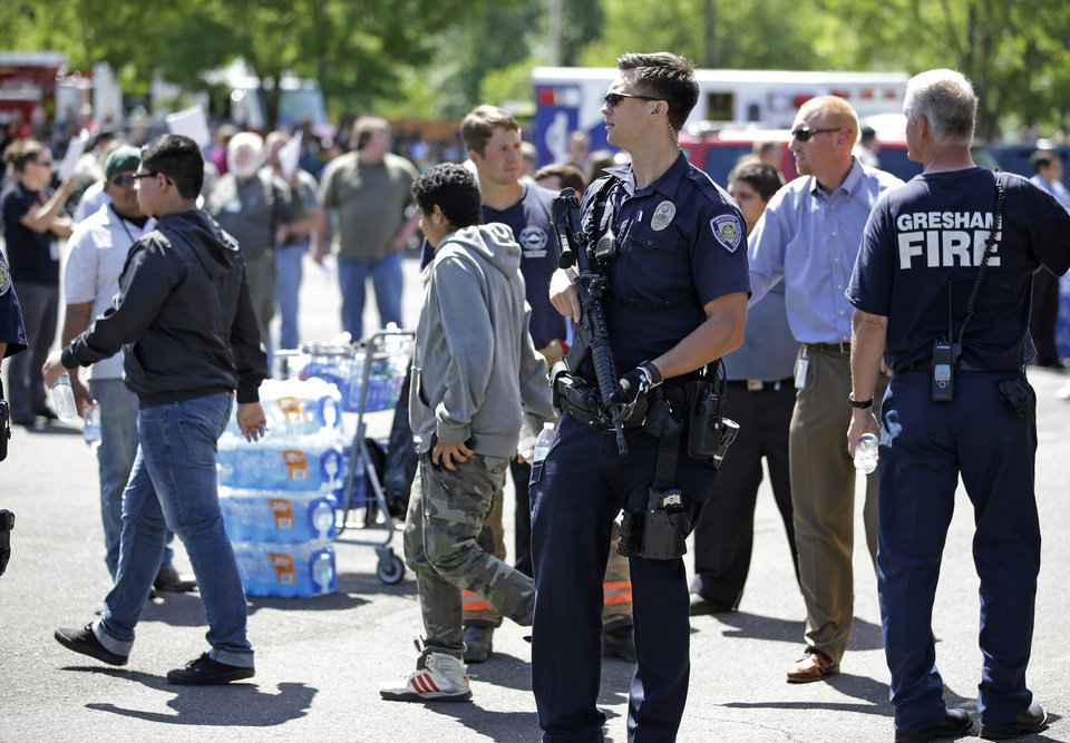 Photo - A police officer stands guard as students arrived by bus at a shopping center parking lot in Wood Village, Ore., after a shooting at Reynolds High School Tuesday, June 10, 2014, in nearby Troutdale. A gunman killed a student at the high school east of Portland Tuesday and the shooter is also dead, police said. (AP Photo/Rick Bowmer)