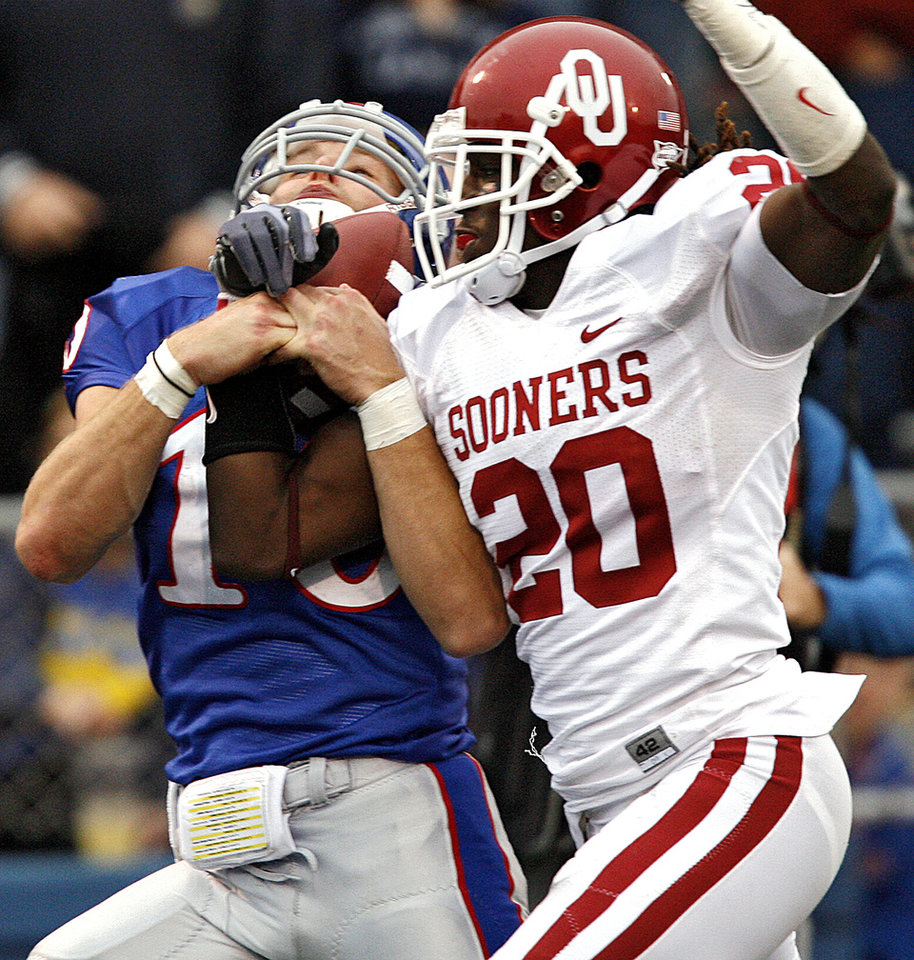 Photo - Oklahoma's Quinton Carter (20) breaks up a pass for Kansas' Kerry Meier (10) during the second half of the college football game between the University of Oklahoma Sooners (OU) and the University of Kansas Jayhawks (KU) on Saturday, Oct. 24, 2009, in Lawrence, Kan. Oklahoma won the game 35-13. Photo by Chris Landsberger, The Oklahoman