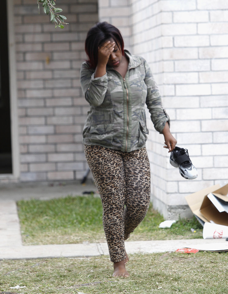 Photo - A distraught family member leaves the house at 7318 Enchanted Creek in Cypress, Texas,Sunday, Nov. 10, 2013, after two people were killed and at least 22 others were injured when gunfire rang out at a large house party in a Houston suburb, sending partygoers fleeing in panic, authorities said. Authorities say they're seeking two gunmen. (AP Photo/Bob Levey)
