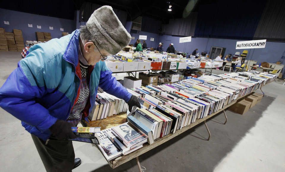 Photo - Larry Eberhardt, Okla. City, sorting books on  the autobiography table Tuesday, Feb. 16, 2010, for the annual Friends of the Library book sale this weekend in Oklahoma City. Photo by Paul B. Southerland, The Oklahoman