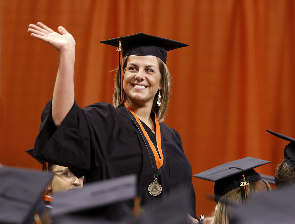 A student stands to wave at friends in the upper level after returning to her seat with her diploma. Undergraduates at OSU participated in the school's 127th commencement ceremony the weekend of Friday, May 3 and Saturday, May 4, 2013 inside Gallagher-Iba Arena on the university's campus.These photos were taken at the Saturday morning ceremony when students from the College of Agricultural Sciences and Natural Resources, and the Spears School of Business were conferred with degrees.   Photo  by Jim Beckel, The Oklahoman.