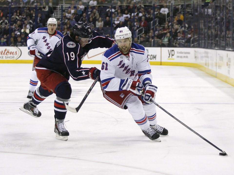 Photo - Columbus Blue Jackets' Ryan Johansen (19) checks New York Rangers' Rick Nash (61) during the first period of an NHL hockey game, Friday, March 21, 2014, in Columbus, Ohio. (AP Photo/Mike Munden)
