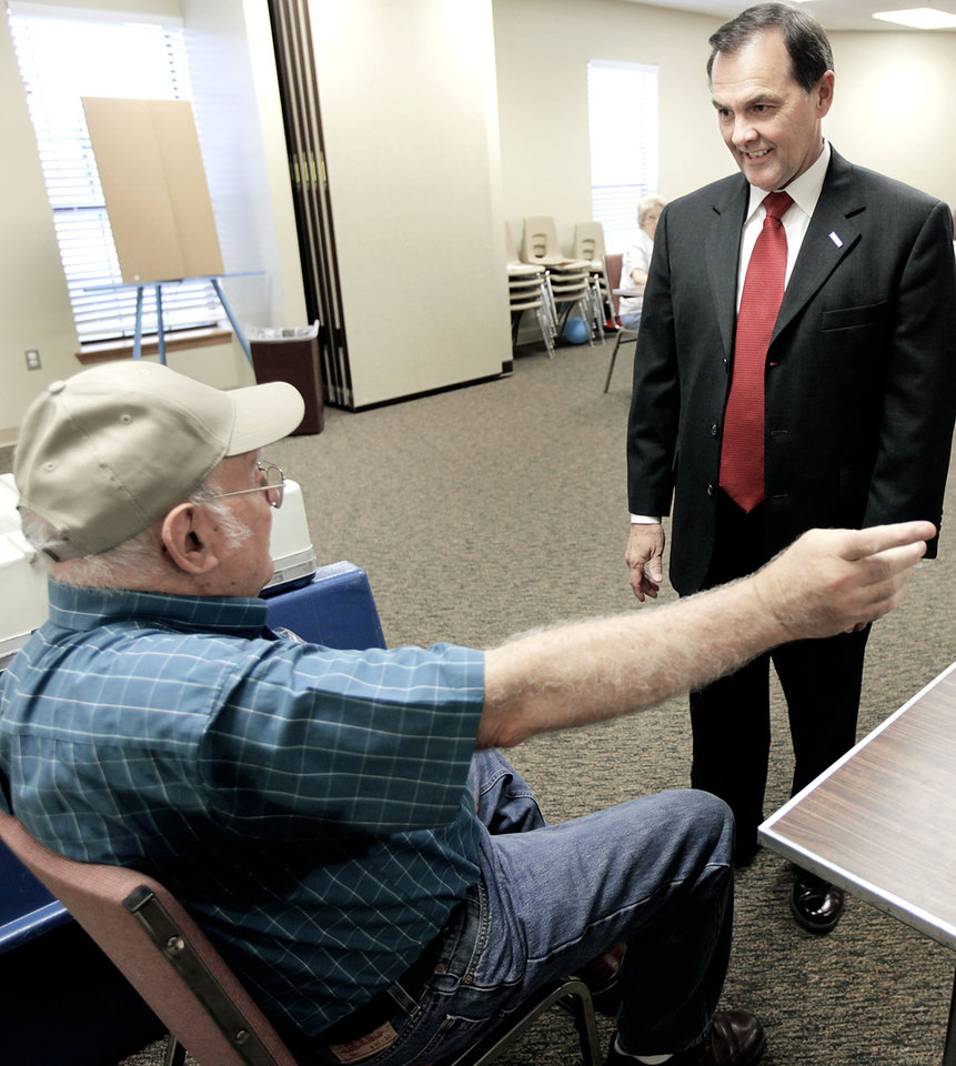Photo - Randy Brogdon visits with inspector Wayne Harvey as he arrives to vote in the Oklahoma primary election at Faith Lutheran Church in Owasso  July 27, 2010. MIKE SIMONS/Tulsa World