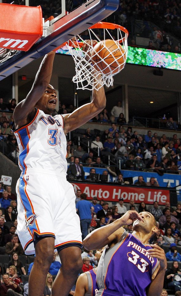 Photo - Oklahoma City's Kevin Durant (35) dunks the ball over Phoenix's Grant Hill (33) after getting a pass from Russell Westbrook (not pictured) in the third quarter during the NBA basketball game between the Oklahoma City Thunder and Phoenix Suns at Chesapeake Energy Arena in Oklahoma City, Saturday, Dec. 31, 2011. Oklahoma City won, 107-97. Photo by Nate Billings, The Oklahoman