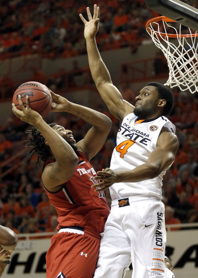 Photo - Oklahoma State's Brian Williams (4) defends as Aaron Ross (15) shoots a lay up during the men's college basketball game between Oklahoma State and Texas Tech at Gallagher-Iba Arena in Stillwater, Okla., Saturday, Feb. 22, 2014. OSU won 84-62. 