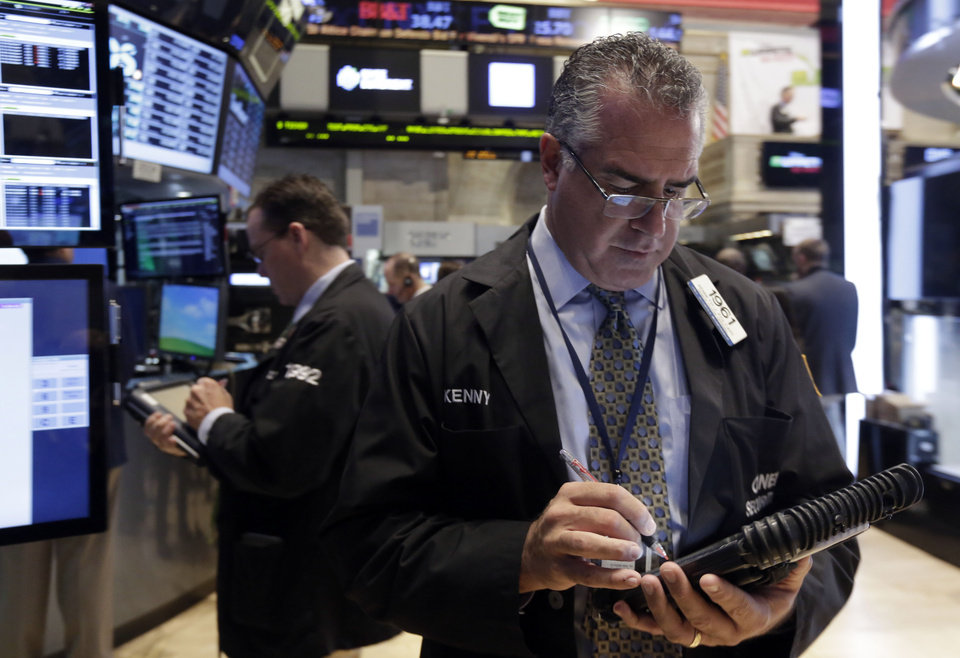 Photo - Trader Kenneth Polcari, right, works on the floor of the New York Stock Exchange Monday, March 17, 2014. Stocks are sharply higher in early trading following news that output at U.S. factories surged last month. (AP Photo/Richard Drew)