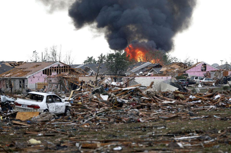 CORRECTS TORNADO MEASUREMENT TO NUMBER REPORTED BY THE NATIONAL WEATHER SERVICE - A fire burns in the Tower Plaza Addition in Moore, Okla., following a tornado Monday, May 20, 2013. A tornado as much as half a mile wide with winds up to 200 mph roared through the Oklahoma City suburbs Monday, flattening entire neighborhoods, setting buildings on fire and landing a direct blow on an elementary school. (AP Photo Sue Ogrocki)