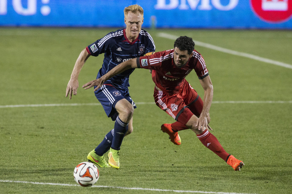 Photo - Toronto FC's Gilberto Sousa, right,  battles for the ball with Chicago Fire's Jeff Larentowicz during the second half of a soccer game, Saturday, Aug. 23, 2014 in Toronto. (AP Photo/The Canadian Press, Chris Young)