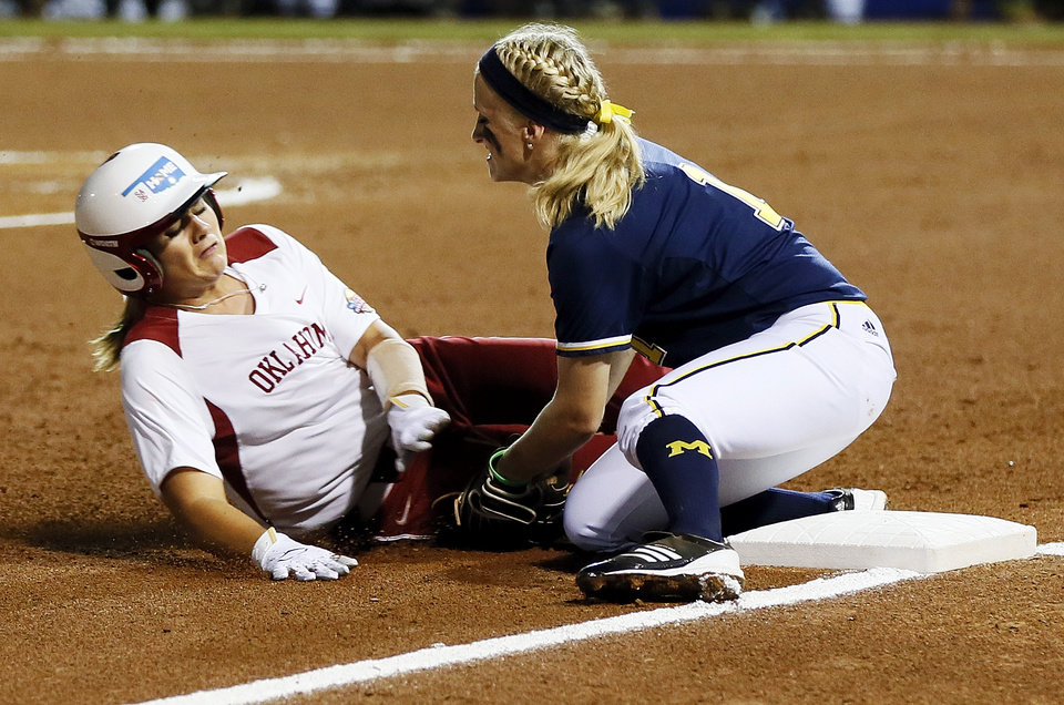 Photo - OU's Georgia Casey (42) is out as she slides into Michigan's Amy Knapp (1) in the first inning during an NCAA softball game in the Women's College World Series between Oklahoma and Michigan at ASA Hall of Fame Stadium, Thursday, May 30, 2013. Photo by Nate Billings, The Oklahoman