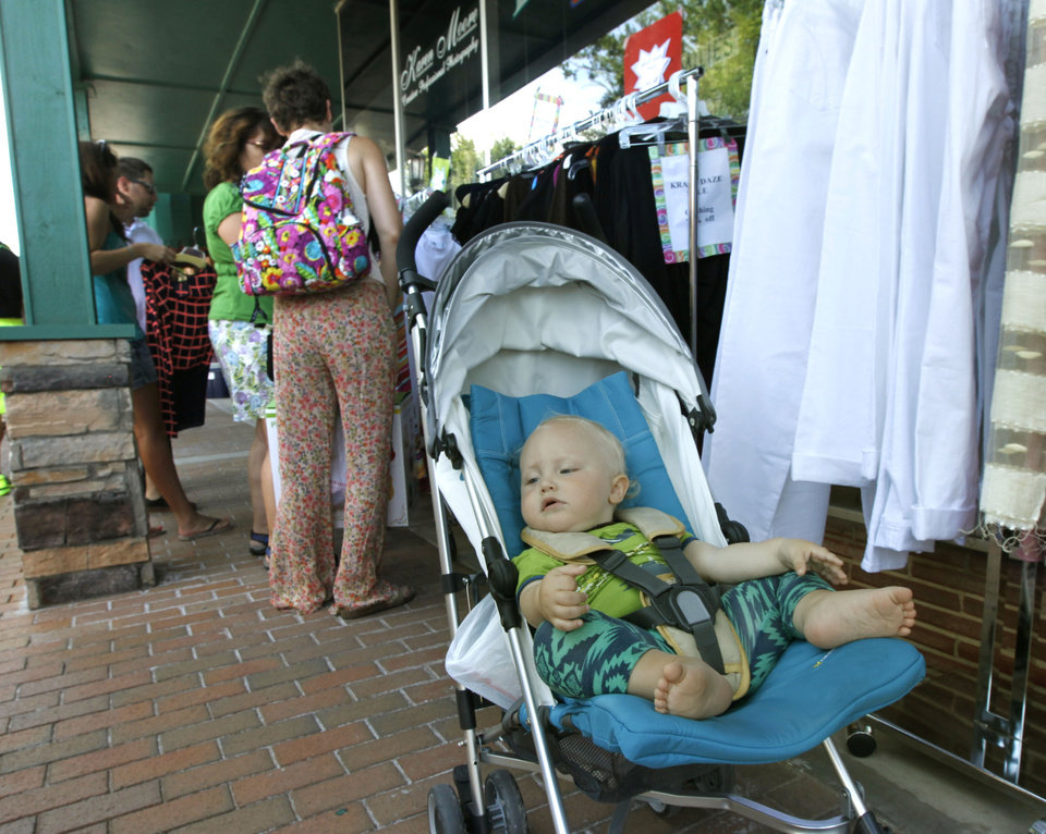 Photo -  Cameron Constance, 1, takes in all the sights as his mother, Anna Constance, and aunt, Gina Houston, look for bargains during the annual Krazy Daze celebration in downtown Edmond. PHOTO BY PAUL HELLSTERN, THE OKLAHOMAN   PAUL HELLSTERN -