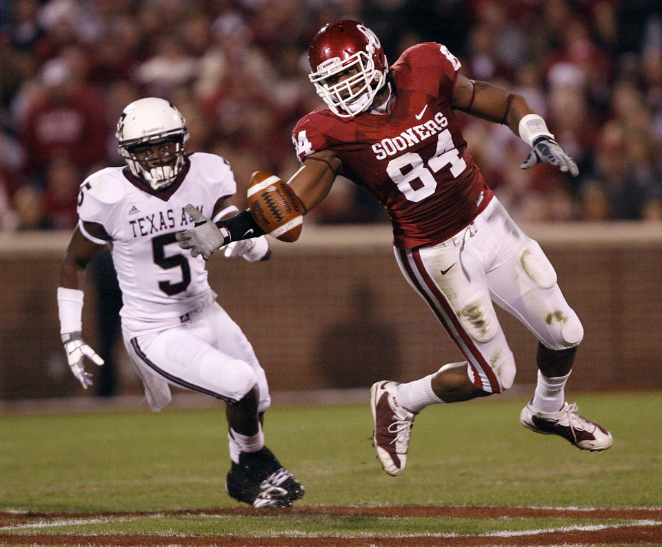 Photo - Oklahoma's Frank Alexander (84) breaks up a pass for Texas A&M's Howard Morrow (5) during the first half of the college football game between the University of Oklahoma Sooners (OU) and the Texas A&M Aggies at Gaylord Family-Memorial Stadium on Saturday, Nov. 14, 2009, in Norman, Okla. 