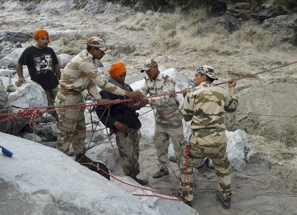 Photo - Indo-Tibetan Border Police (ITBP) use a rope to rescue stranded pilgrims, in saffron turban, cross a river swollen by flood waters at Ghangaria, in northern Indian state of Uttarakhand, India. Rescuers found 40 bodies floating in the River Ganges near a Hindu holy city on Friday, sending the death toll past 200 from flooding in northern India that has stranded tens of thousands of people, mostly Hindu pilgrims, since heavy monsoon rains began about a week ago. (AP Photo)
