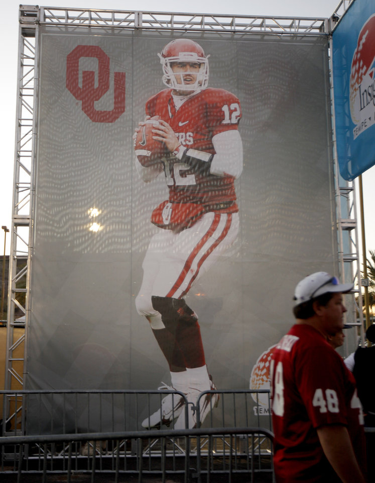 Photo - Fans walk past a poster of Landry Jones before the Insight Bowl college football game between the University of Oklahoma (OU) Sooners and the Iowa Hawkeyes at Sun Devil Stadium in Tempe, Ariz., Friday, Dec. 30, 2011. Photo by Bryan Terry, The Oklahoman