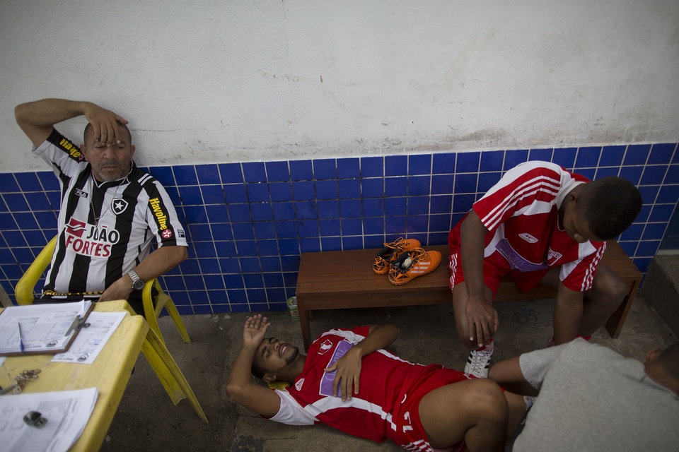 Photo - In this April 27, 2014 photo, Bayer's Vagner Vieira, 25, lies on the floor as he is attended by teammates after he was injured at an amateur soccer match in the Vila da Penha neighborhood of Rio de Janeiro, Brazil. Brazil is a five-time champion of the World Cup, and will host this year's international soccer tournament starting June 12. In Brazil, soccer is a unifying force. (AP Photo/Leo Correa)