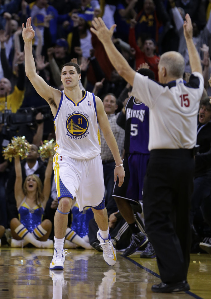 Photo - Golden State Warriors' Klay Thompson (11) celebrates after scoring in the final seconds  of an NBA basketball game against the Sacramento Kings Wednesday, March 6, 2013, in Oakland, Calif. (AP Photo/Ben Margot)