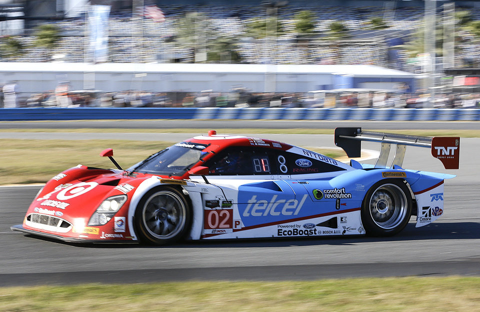 Photo - Scott Dixon, of New Zealand, drives the Ganassi Riley DP out of a turn as he leads the IMSA Series Rolex 24 hour auto race in the early hours at Daytona International Speedway in Daytona Beach, Fla., Saturday, Jan. 25, 2014. (AP Photo/John Raoux)