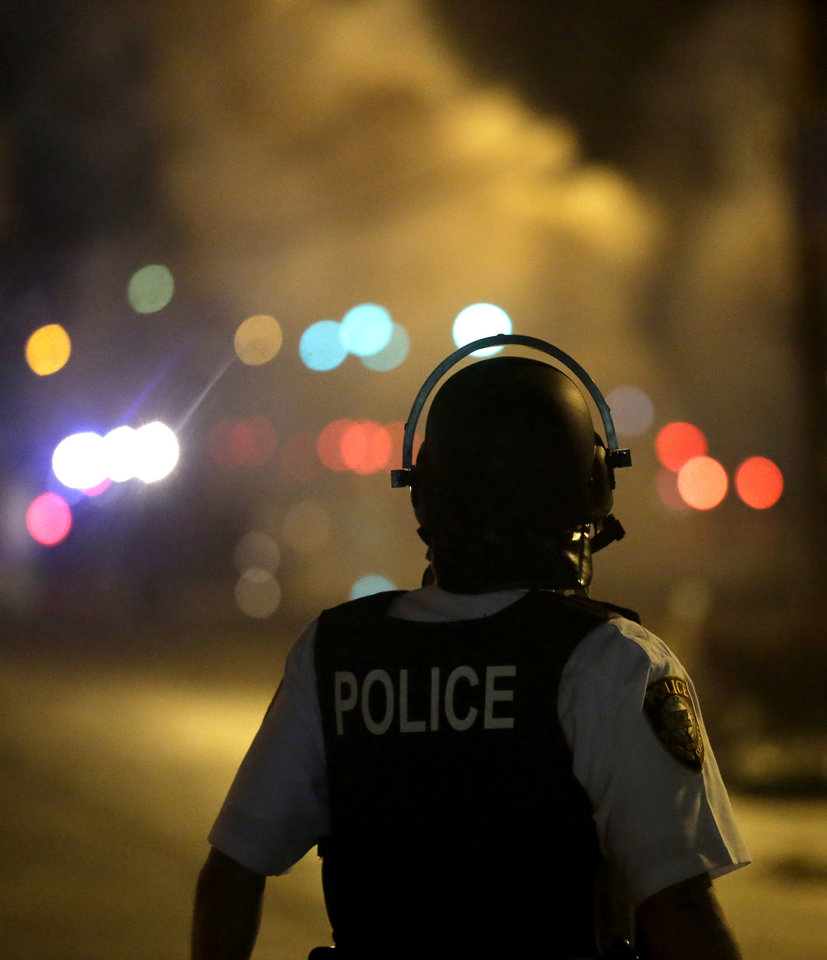Photo - A law enforcement officer watches Sunday, Aug. 17, 2014, after tear gas was fired to disperse a crowd protesting the shooting of teenager Michael Brown last Saturday in Ferguson, Mo. Brown's shooting in the middle of a street following a suspected robbery of a box of cigars from a nearby market has sparked a week of protests, riots and looting in the St. Louis suburb. (AP Photo/Charlie Riedel)
