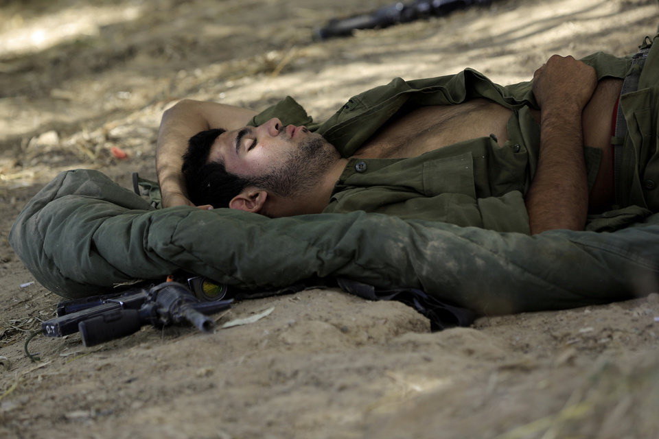 Photo - An Israeli soldier sleeps near the border of Israel and Gaza, Friday, July 18, 2014. Israeli troops pushed deeper into Gaza on Friday to destroy rocket launching sites and tunnels, firing volleys of tank shells and clashing with Palestinian fighters in a high-stakes ground offensive meant to weaken the enclave's Hamas rulers. Israel launched the operation late Thursday, following a 10-day campaign of more than 2,000 air strikes against Gaza that had failed to halt relentless Hamas rocket fire on Israeli cities. (AP Photo/Tsafrir Abayov)