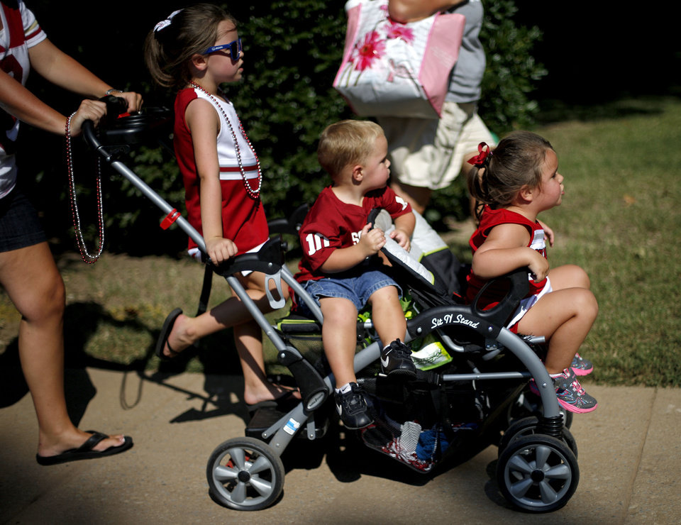 Photo - Mackenzie McKay, 5, left, Mason Moreno, 2, and Madison Moreno, 3, get a ride outside the stadium before a college football game between the University of Oklahoma Sooners (OU) and the West Virginia University Mountaineers at Gaylord Family-Oklahoma Memorial Stadium in Norman, Okla., on Saturday, Sept. 7, 2013. Photo by Bryan Terry, The Oklahoman