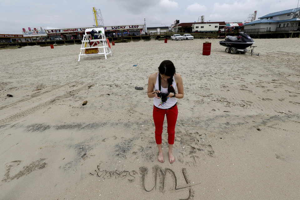 Photo - In this Friday, May 24, 2013 photo, Jasmine Wilker, 15, of Robbinsville, N.J., takes a photograph of writing she put on the sand on the beach, in Seaside Heights, N.J. The Jersey Shore beaches officially opened for the summer on Friday, after rebuilding following the destruction left behind by Superstorm Sandy last fall. The storm caused $37 billion of damage in the state. (AP Photo/Julio Cortez)