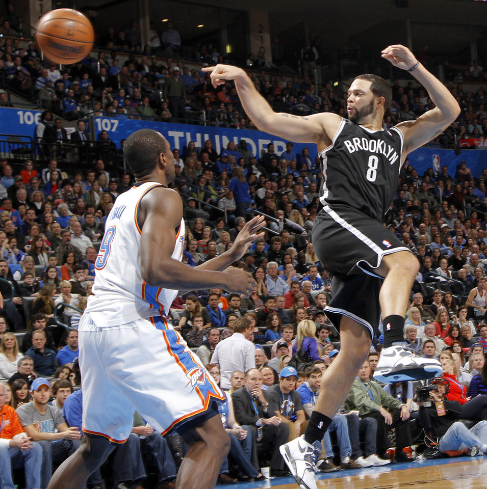 Photo - Brooklyn Nets' Deron Williams (8) passes the ball over Oklahoma City's Serge Ibaka (9) during the NBA basketball game between the Oklahoma City Thunder and the Brooklyn Nets at the Chesapeake Energy Arena on Wednesday, Jan. 2, 2013, in Oklahoma City, Okla. Photo by Chris Landsberger, The Oklahoman