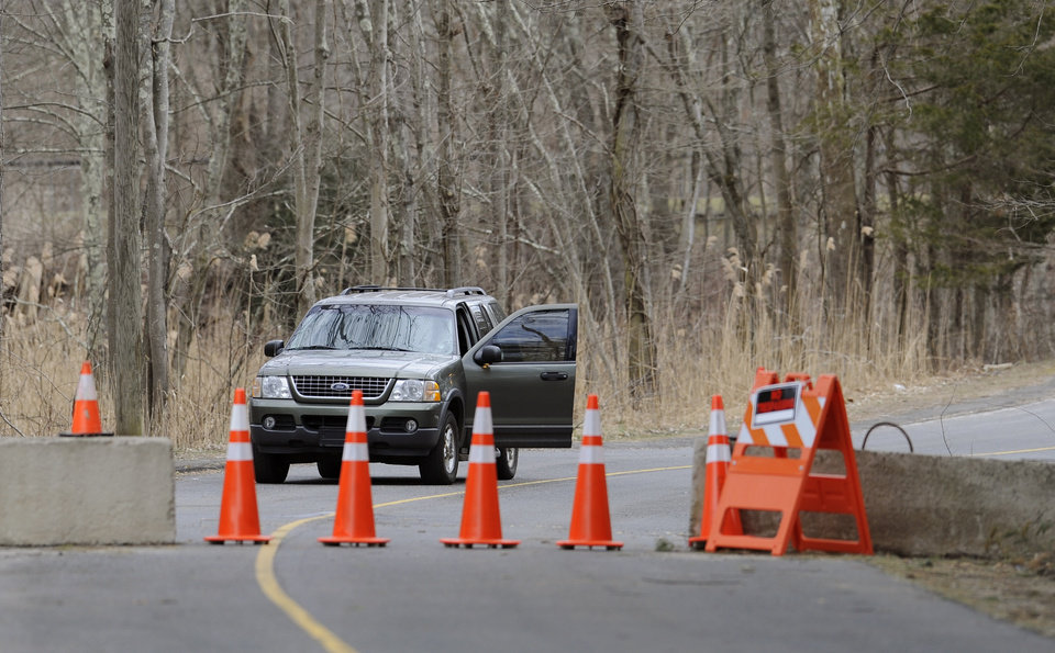 Photo - A guard stands watch behind cones and concrete barrier at the entrance to Sandy Hook Elementary School in Newtown, Conn., Thursday, March 28, 2013. Search warrants released Thursday, March 28, 2013, revealed that an arsenal of weapons including guns, more than a thousand rounds of ammunition, a bayonet and several swords was seized at Adam Lanza's home.  Lanza killed his mother, Nancy Lanza in their home before he forced his way into Sandy Hook Elementary School in Newtown, Conn, killing 26 people. (AP Photo/Jessica Hill)