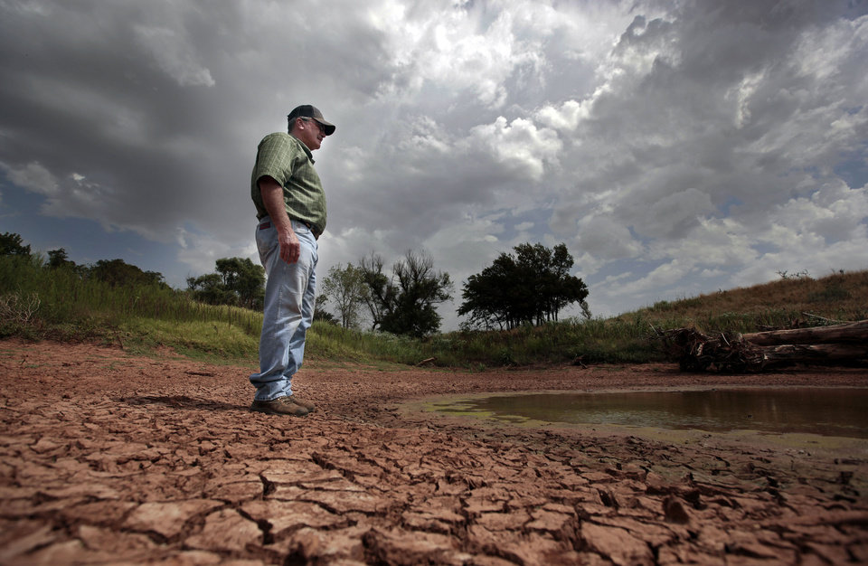 Fred Reuter looks over a nearly dry pond Thursday on his property near El Reno. The farmer and rancher said the past two years of drought have brought conditions he�s never seen before. Photo by Sarah Phipps, The Oklahoman