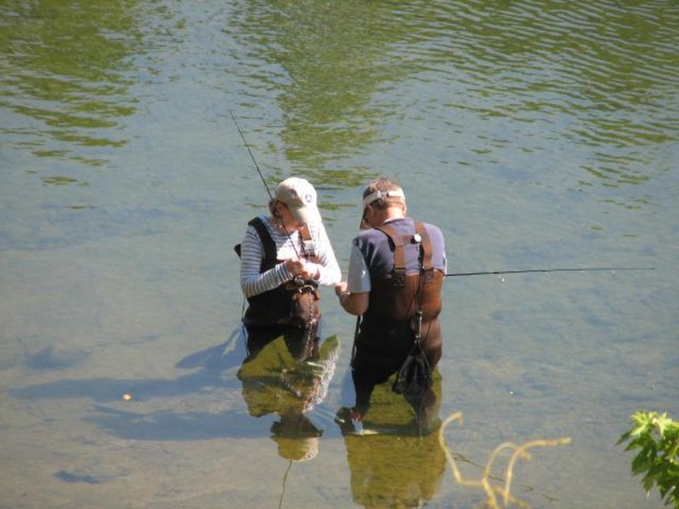 Photo - A couple of trout anglers prepare their fishing tackle on the White River. PHOTO BY ED GODFREY, THE OKLAHOMAN
